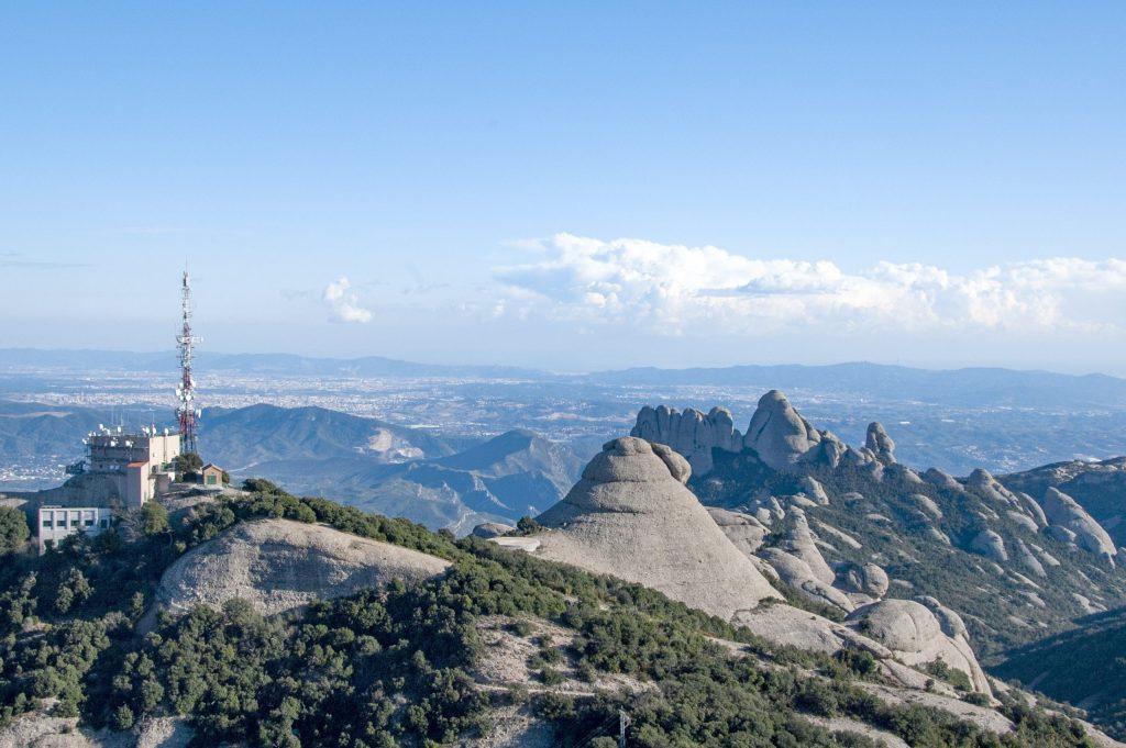 Visió des del cim de sant Jeroni en direcció a la regió dels Flautats amb la roca del Moro a primer pla i l'Estació de Telecomunicacions.